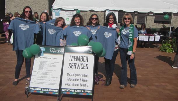 7 women outside holding up tshirts, standing behind folding signs