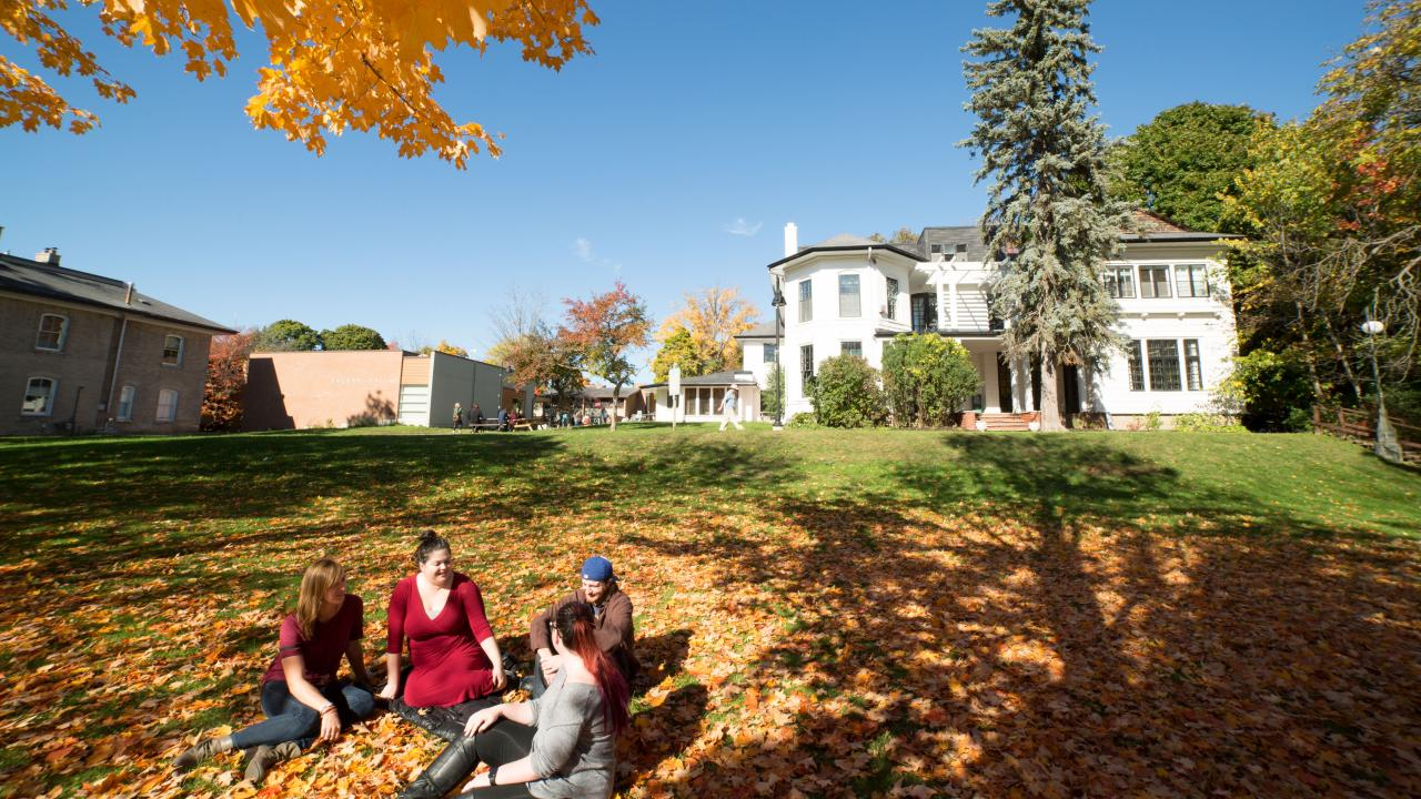 Students sitting on the lawn in front of Scott House at Traill College