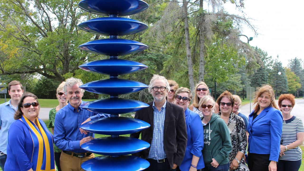 President Leo Groarke stands with artist Shayne Dark beside his sculpture entitled This Column Ends outside Blackburn College with a group of people.