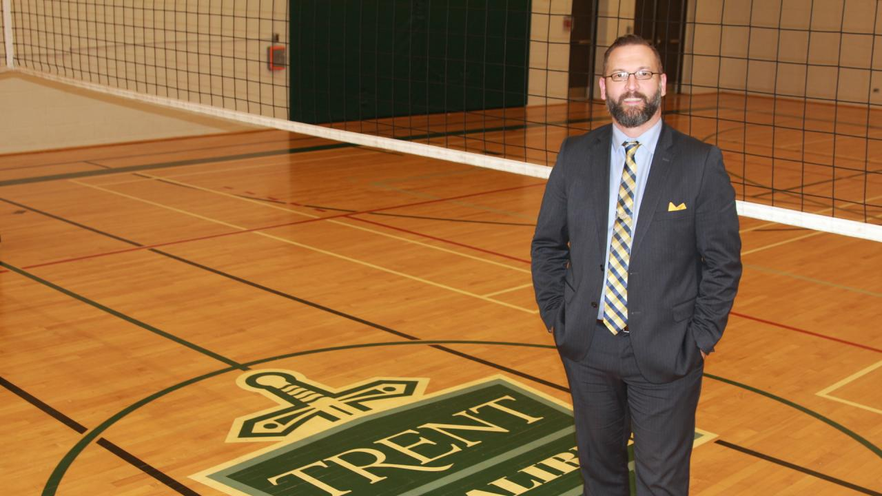 Rusty Haines stands on the volleyball court wearing a suit and a yellow and blue striped tie.