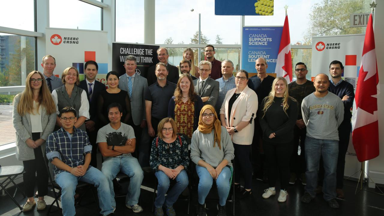 University researchers pose as a group with the Honourable Maryam Monsef after the announcement of a $558 million investment in research from NSERC, the largest in discovery science grants in Canadian history.