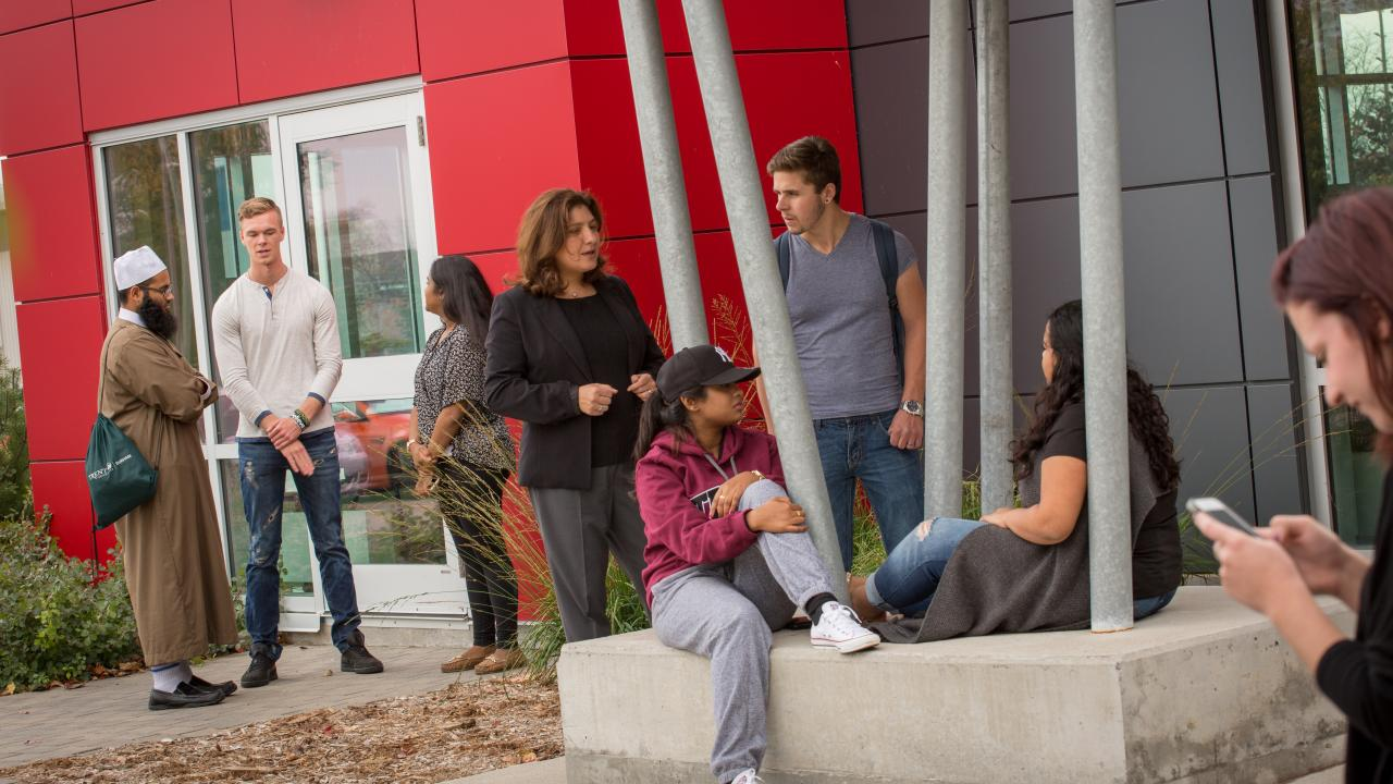 People conversing outside of the Trent University Durham Campus building.