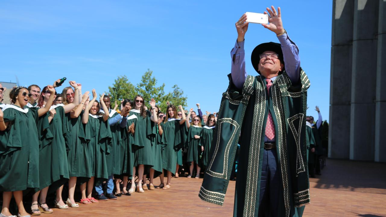 Don Tapscott taking a selfie with graduating Trent University students