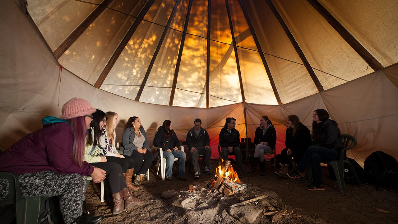 Students gathered in tipi on campus.
