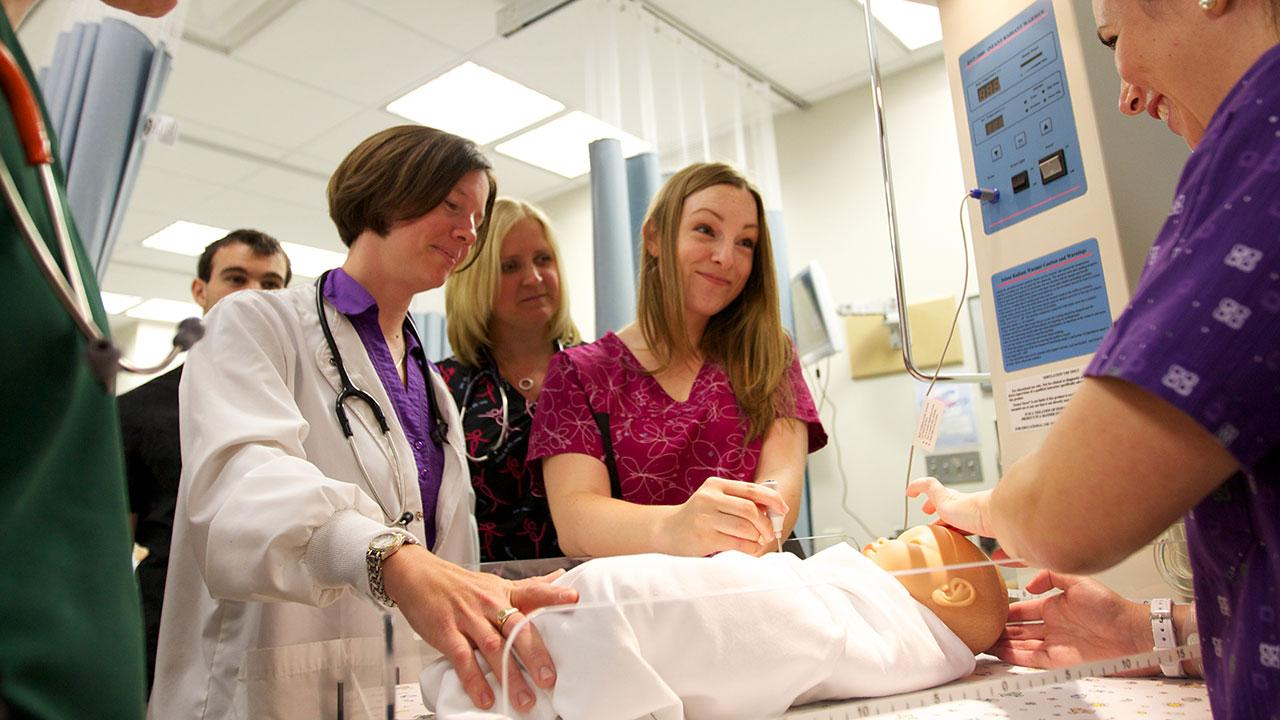 Trent University students participating in a Nursing lab simulation alongside instructors.