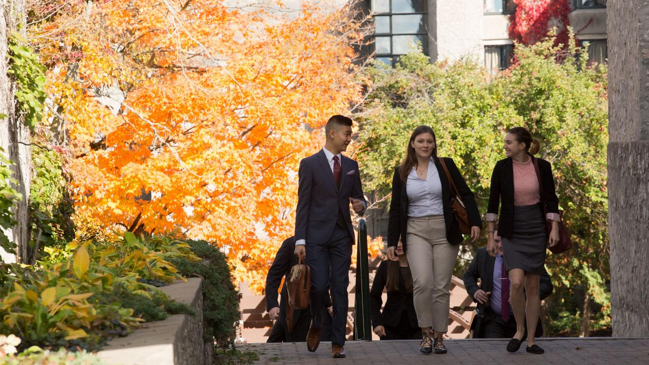 Business students walking together and talking on campus.