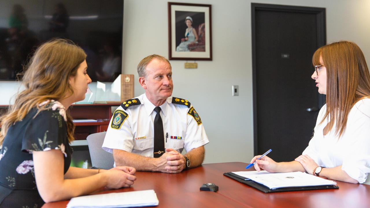 Trent students Samantha Groulx and Raquel Maset meet with police Chief Scott Gilbert.
