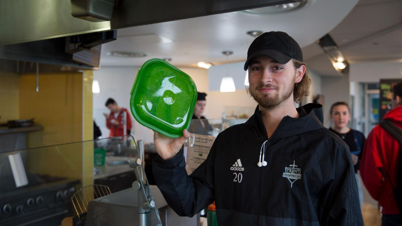 Trent University student holds up re-usable green container at Gzowski dining hall.