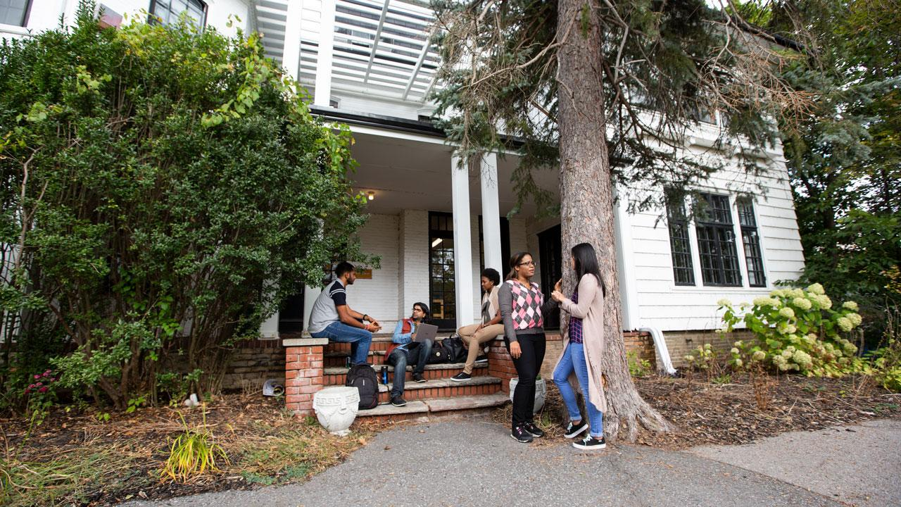 Trent University students conversing outside of Scott House at Traill College, Trent University.