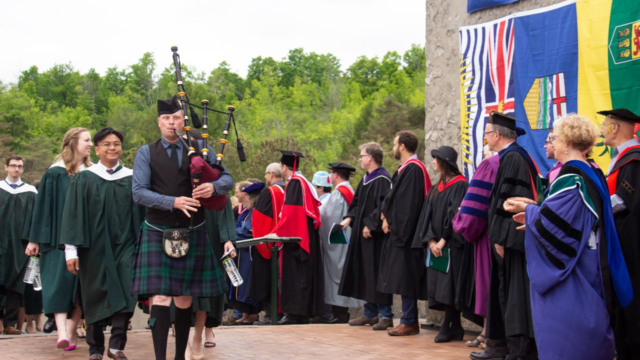Students process past faculty as the piper leads the way.