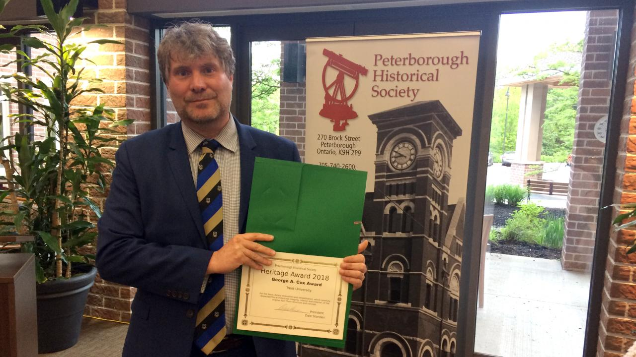 Dr. Michael Eamon, Co-Chair of the university's Heritage Stewardship Committee poses for a photo with the Heritage Award certificate.