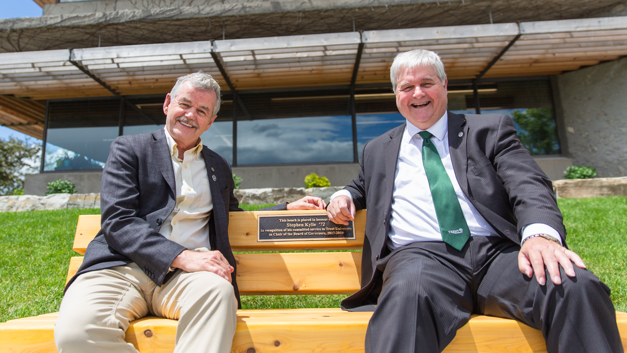 President Leo Groarke sits with Stephen Kylie on the bench that has been dedicated in recognition of Mr. Kylie's service to Trent University as Chair of the Board of Governors, 2017- 2019.