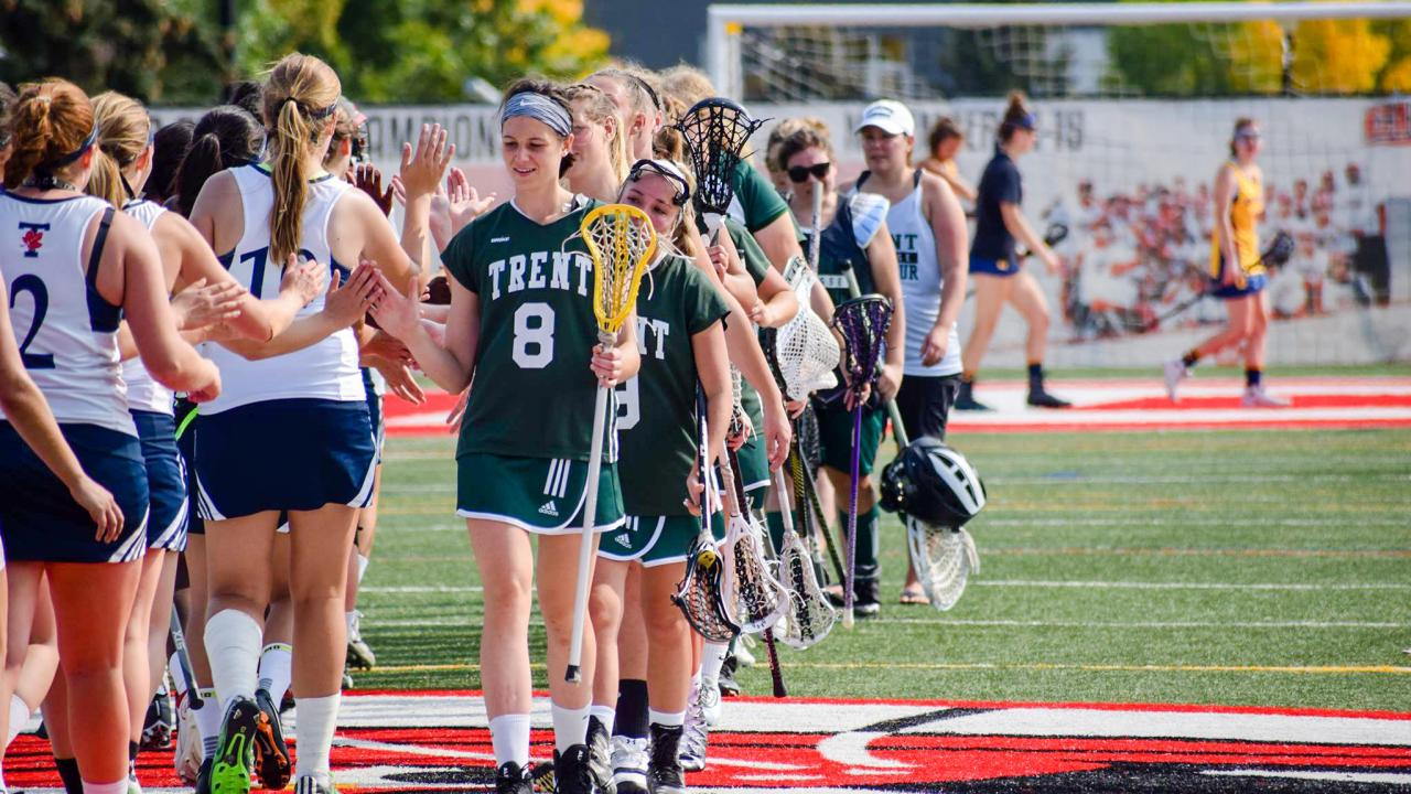 Trent University women's lacrosse team shaking hands with opponents after a game.