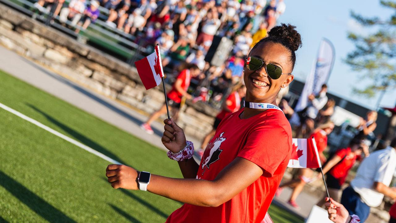 Canadian Women's Lacrosse team member waving the flag and smiling at the U10 World Lacrosse Opening Ceremonies at Trent University.