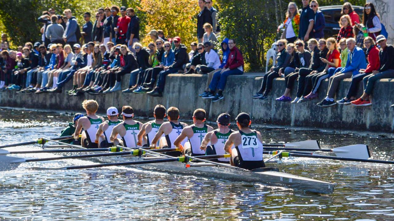 8 men in row boat with spectators watching them race