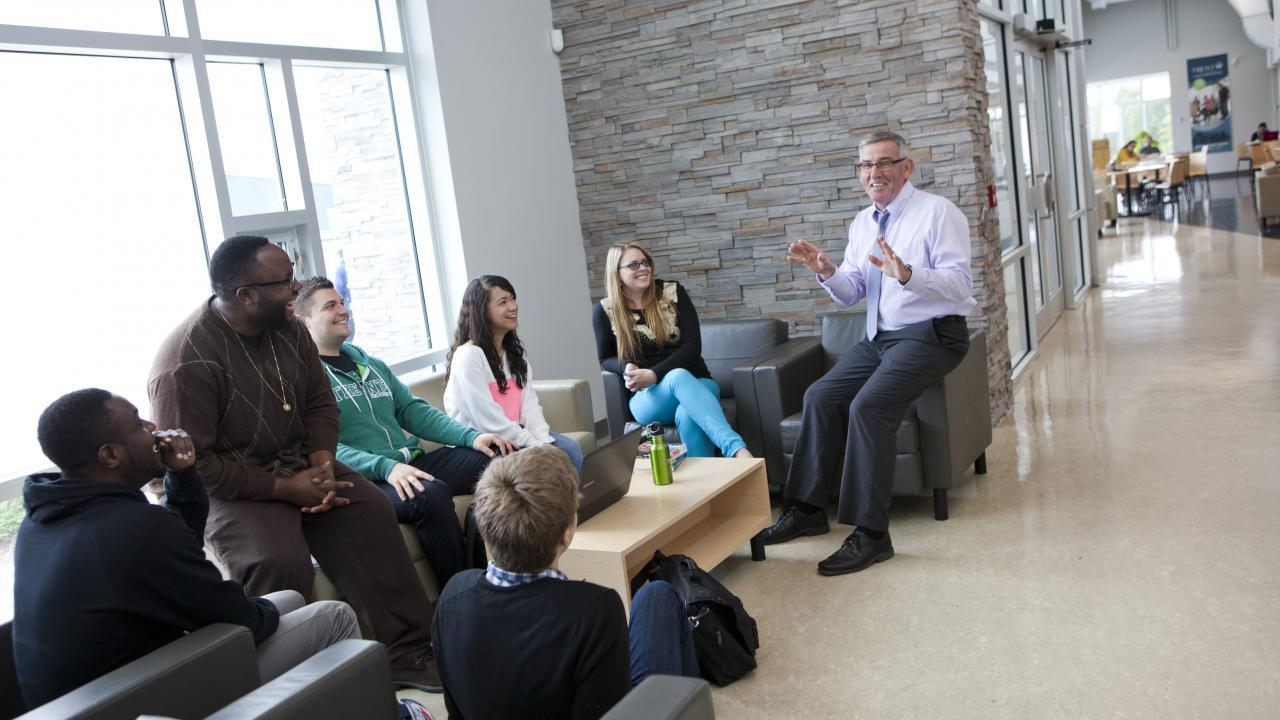 Students and faculty engage in discussion in the Durham GTA atrium