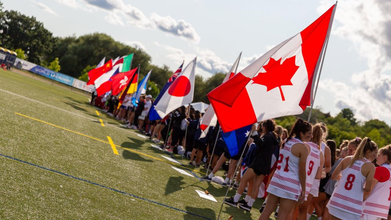 The U19 women's lacrosse teams holding their nation's flags at the closing ceremonies