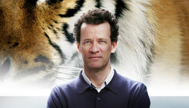 Head and shoulders photo of Yann Martel looking at the camera, wearing a blue sweater, with a graphic of a tiger behind him