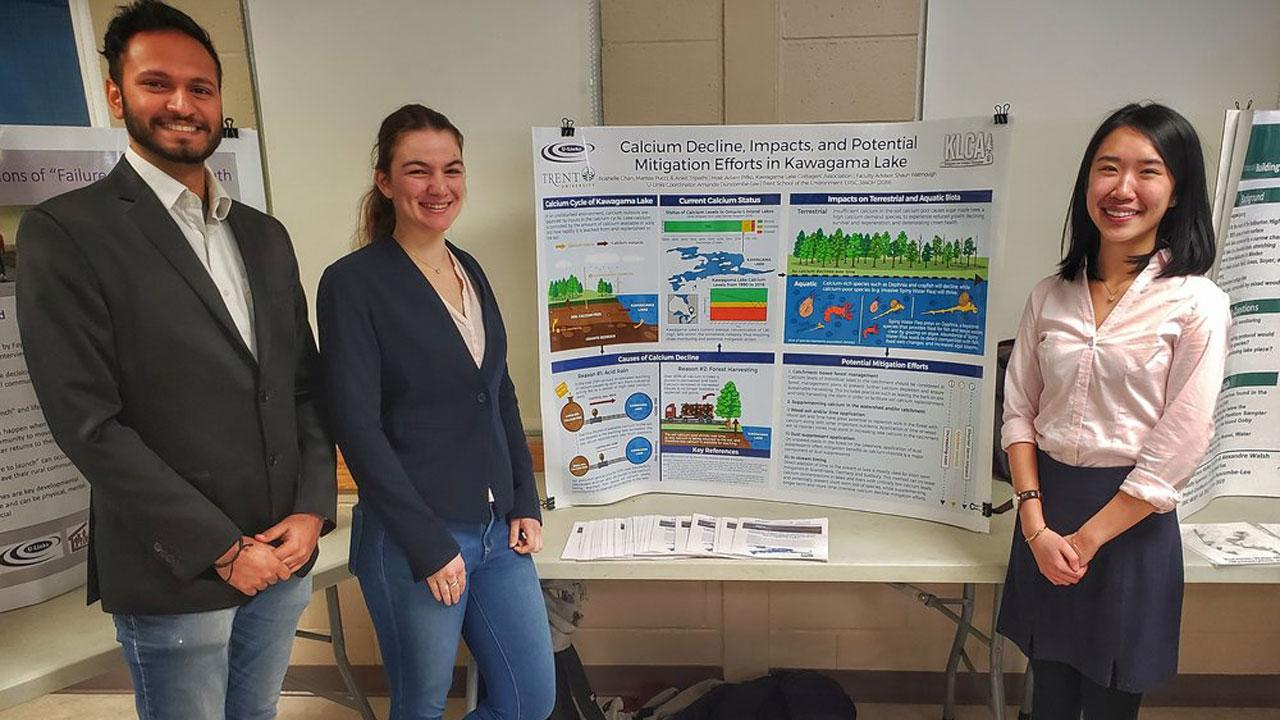 Ankit Tripathi, Marissa Pucci and Roshelle Chan stand in front of their presentation.