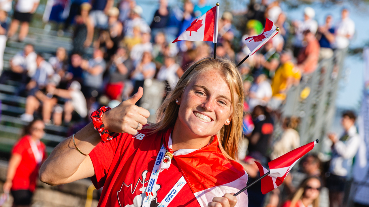 A fan smiles and gives a thumbs up at the U19 World Lacrosse Championship while wearing Canada flags on her headband.