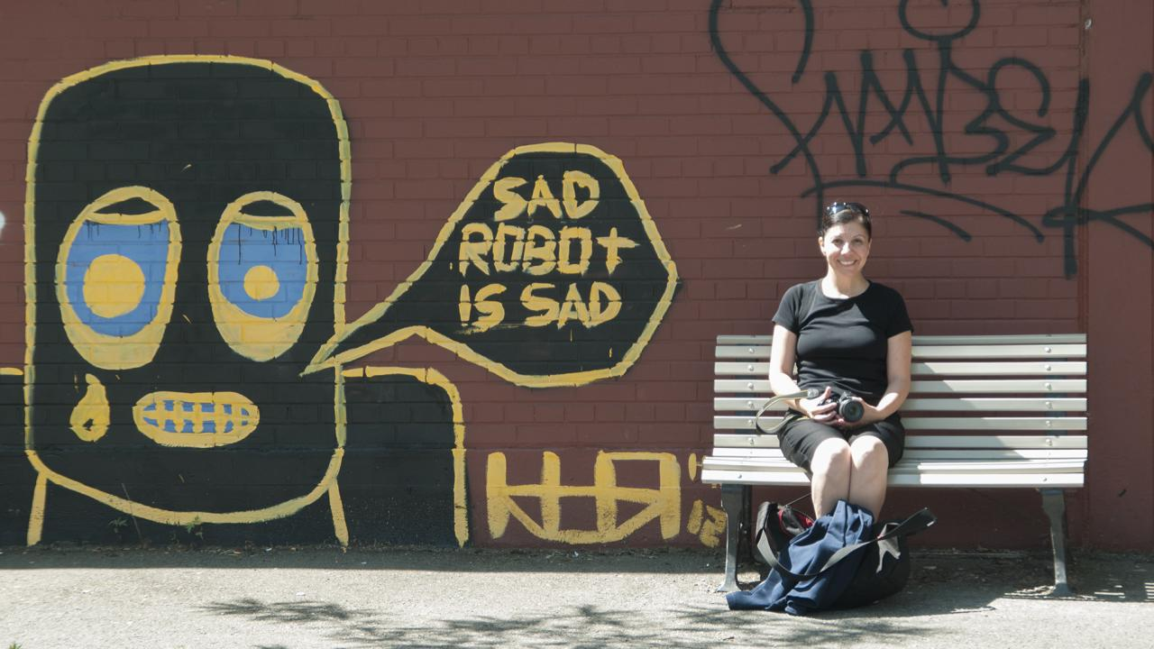 Dr. Anna Augusto Rodrigues, an instructor within the Child and Youth Studies program at Trent University Durham GTA sitting on a bench beside some street art.