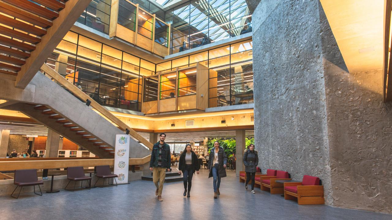 Trent University students walking through the Bata library atrium