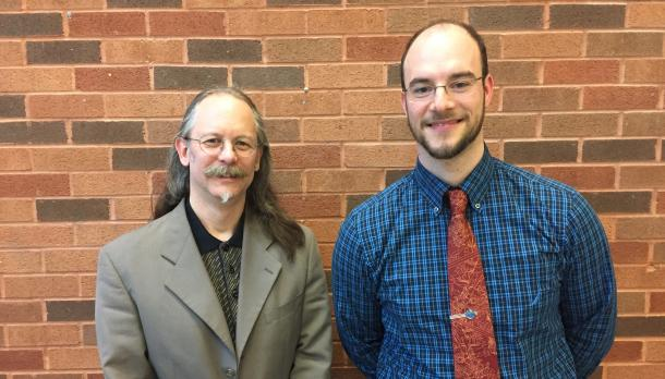 Trent alumnus Shayne Dahl standing beside Dr. Roger Lohmann in front of a brick wall, smiling at the camera