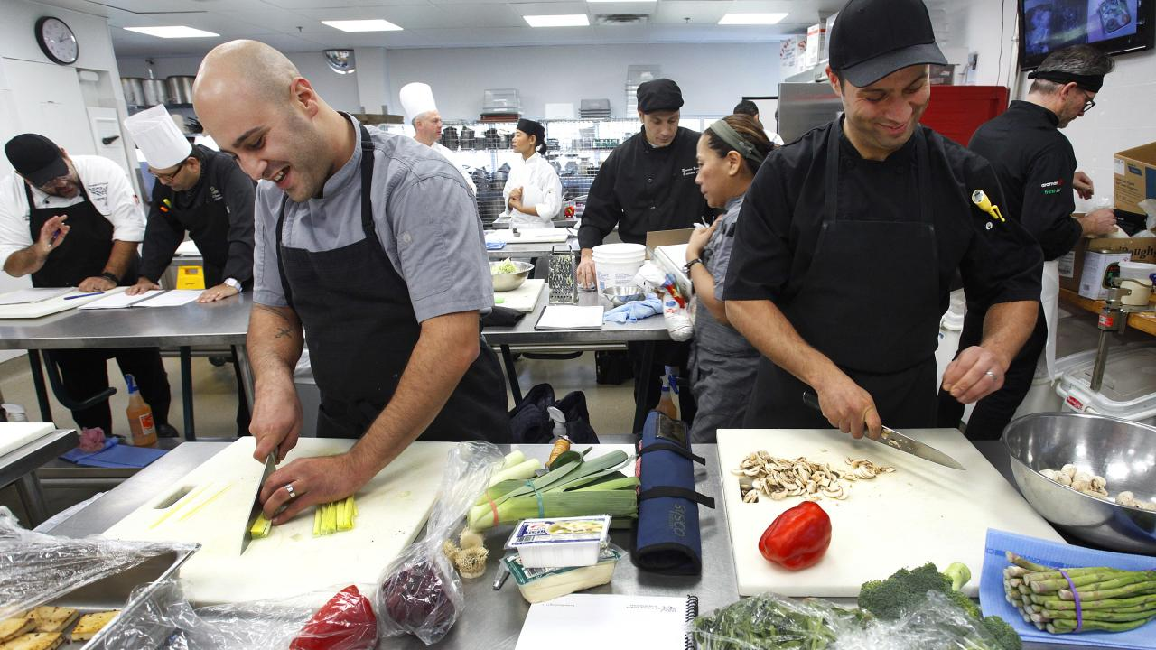 "Two chefs chop veggies to prepare a vegan dish at the ""Forward Food Culinary Experience"" at Fleming College."