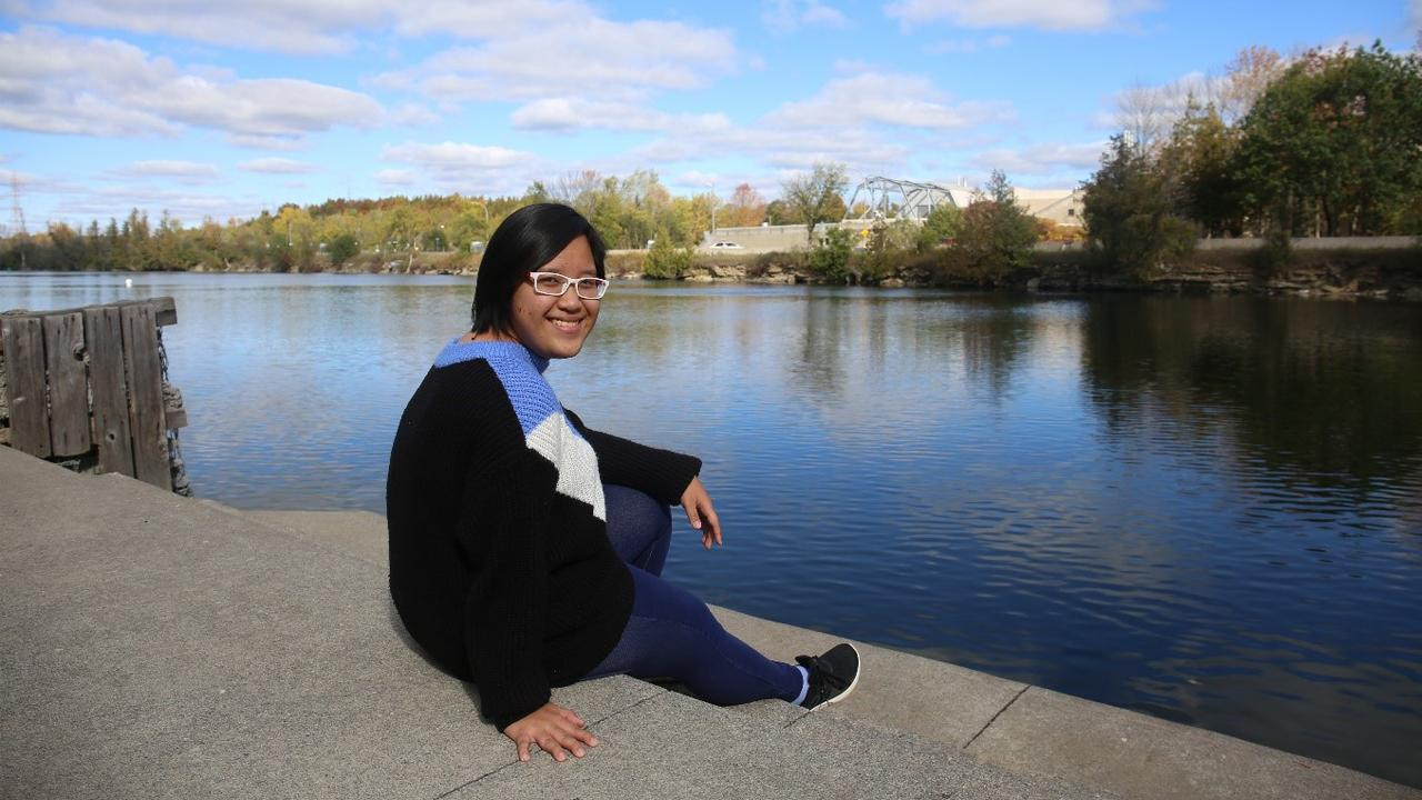 Hang Nguyen, Environmental Chemistry student and international student from Vietnam, enjoying the view of the Otonabee River at Trent University.