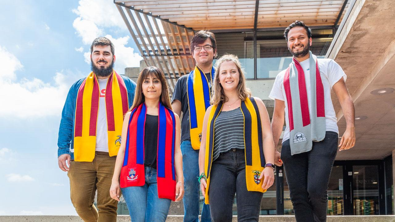 Trent University students representing their colleges wearing their scarves.